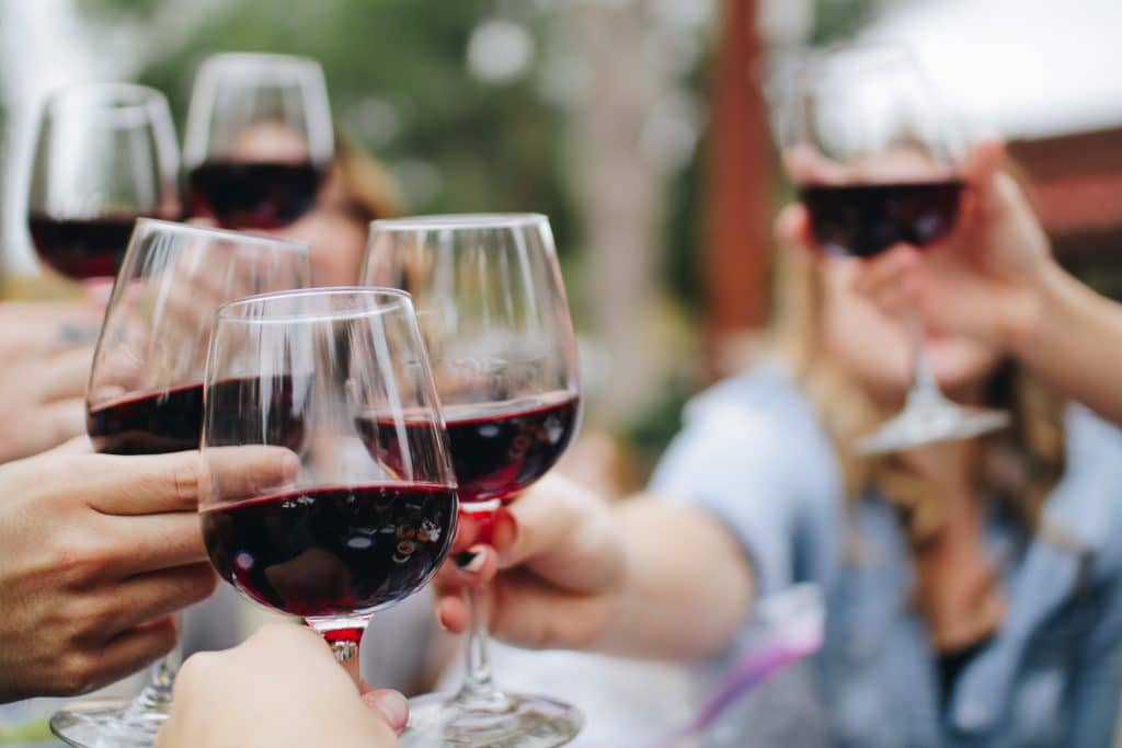 A group of people holding red wine glasses